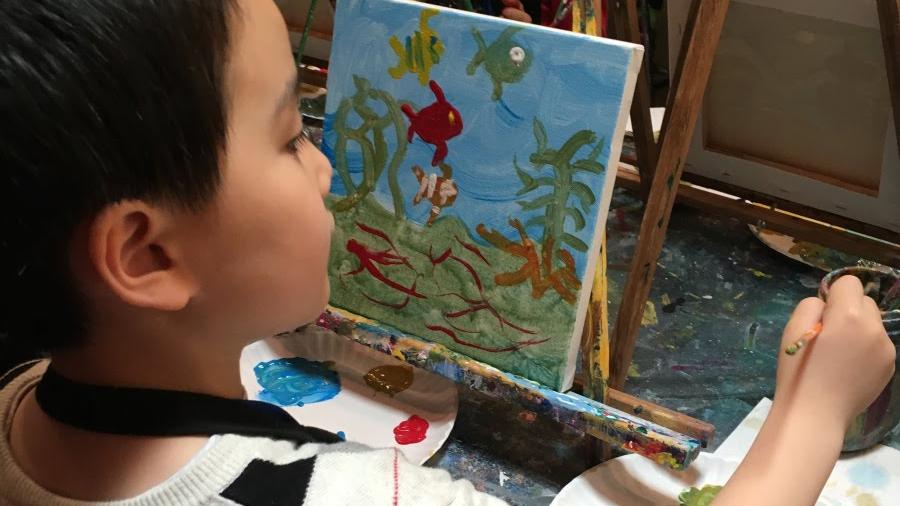 student painting on easels