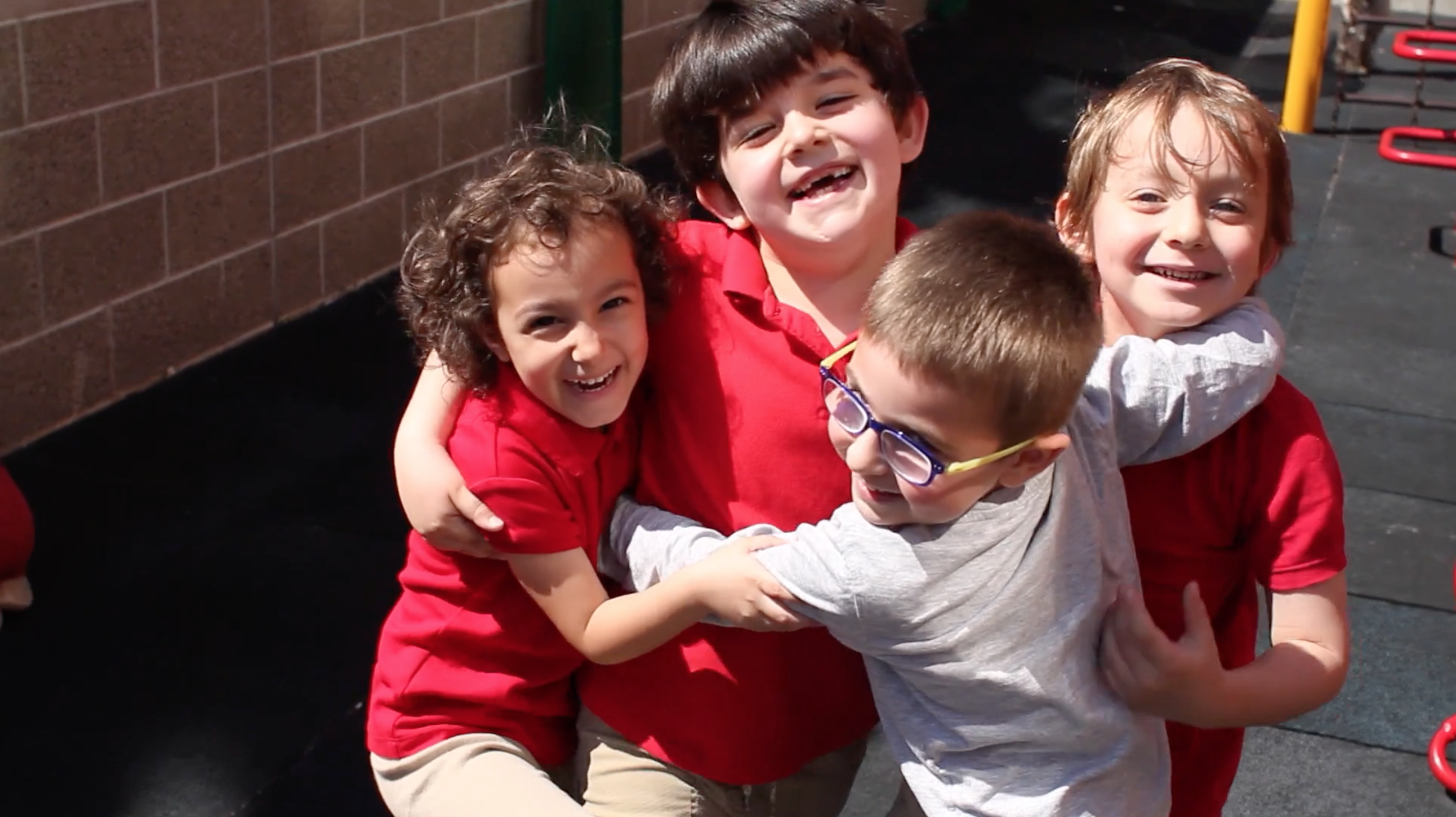 K students hugging on the playground